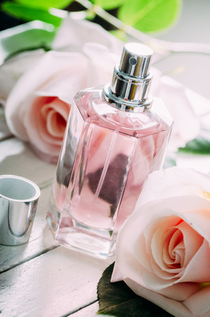 Bottle of perfume and pink wedding roses bouquet decoration.
