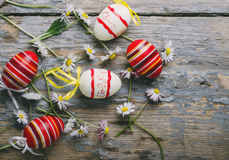 Easter eggs and spring daisy flower on rustic wooden background from above. Top view still life easter concept. Фото со стока