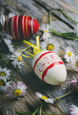 Easter eggs and spring daisy flower on rustic wooden background. Still life easter concept. Фото со стока