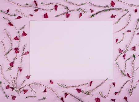 Floral pattern and empty valentine card with flowers and petals over pink background top view. Flat lay frame. Valentines day design greeting card from above.