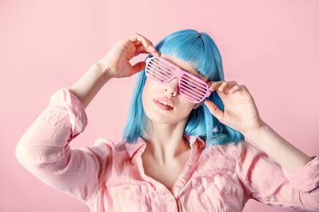 Beautiful young woman with blue color dyed hair with hipster party glasses dancing in front of pastel studio background.