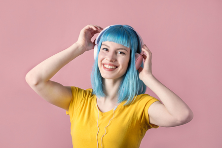 Beautiful smiling young woman with blue color dyed hair with pink headphones listening to music and dance in front of pastel studio background. Фото со стока