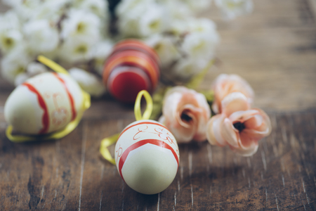 Easter egg and spring blossom flower closeup on rustic wooden table. Easter still life spring decoration.