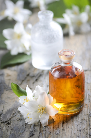 Essential oil with jasmine flower. Aromatherapy massage oil on rustic wooden background.