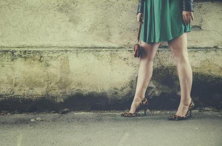 Piedini femminili sexy in tacchi alti moderni che camminano sulla strada. Donna davanti al muro di strada in scarpe tacco alto alla moda con stampa leopardata. Filtro in stile retrò con sfondo copyspace.