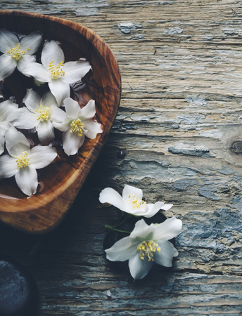 Wellness and spa vintage background. Jasmin flower petals in bamboo wooden bowl with water. Relaxation and body care concept.