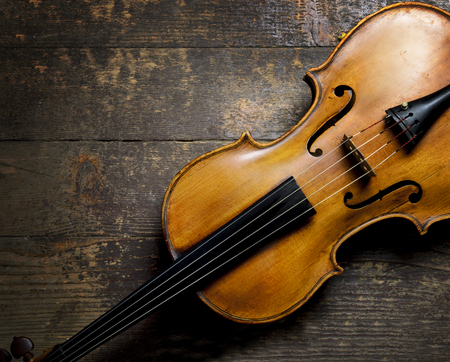 Violin on rustic wooden background from above. Classical musical string instrument. Classic music concept.