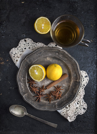 Top view of vintage tea set with aromas and lemon on rustic black background. Food and drink still life. Cup of hot beverage with anise, cinnamon and lemon.