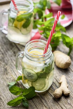 Healthy eating lifestyle concept. Homemade detox lemonade with cucumber, ginger and mint in retro mason jar glass on wooden table. Summer refreshment dring recipe.