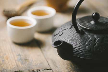 Still life with traditional asian herbal tea prepared in vintage cast iron teapot with organic dry herbs on rustic wooden table.