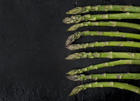 Top view of fresh green asparagus on rustic black board with copyspace. Food and cooking recipe background.