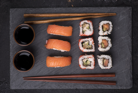 Sushi rolls set with salmon and tuna fish on black sushi board from above. Top view of traditional japanese cuisine. Asian food on black stone slate with chopsticks.