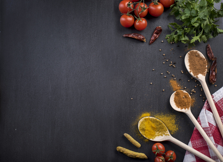 Food ingredients and various spices on black rustic background from above. Cooking and gastronomy concept.