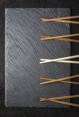 Black sushi slate board with wooden chopsticks with copyspace. Top view. Asian food background.