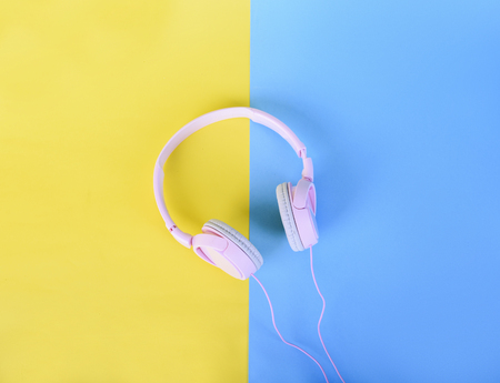 Top view of pink headphones on yellow and blue pastel background. Flat lay music and sound design. Listen to music minimal concept.