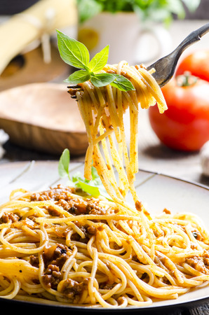 Closeup of italian spaghetti bolognese with basil serve on plate. Traditional homemade italian food recipe. Cooking and gastronomy concept. Standard-Bild