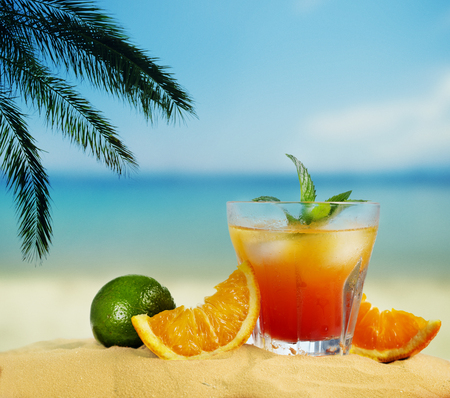 Orange cocktail and citrus fruit on tropical sandy beach. Summer holiday and beach party design. Фото со стока
