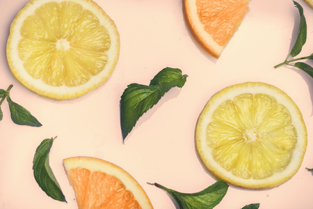 Citrus slices and mint herbs pattern on retro pink background from above. Top view of orange and lemon fruit slices on pastel background. Фото со стока