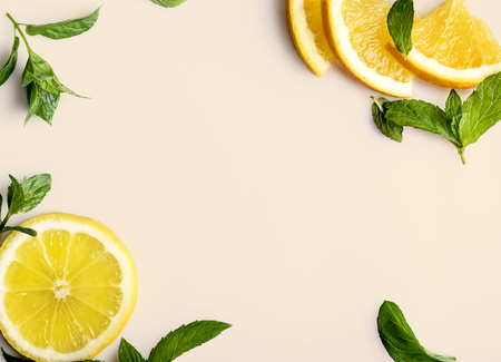 Citrus slices and mint herbs frame on retro pastel  background with copyspace