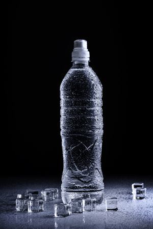 Fresh drinking mineral water in plastic bottle on black background. Healthy living concept. Фото со стока