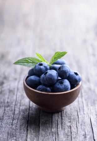 Bowl of fresh blueberries on rustic wooden table. Healthy organic seasonal fruit background. Organic food  blueberries and mint leaf for healthy lifestyle. Фото со стока