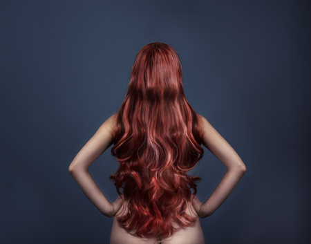 Woman with perfect curly dyed hairstyle from behind. Fashion portrait of red head woman from the back over dark background. Perfect long red hair. Stock Photo