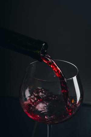 Red wine pouring in wine glass over black background. Closeup of red wine splashing in wineglass in restaurant. Wine tasting.