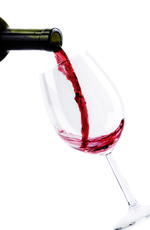 Red wine pouring in wine glass isolated over white background. Red wine splashing in wineglass.