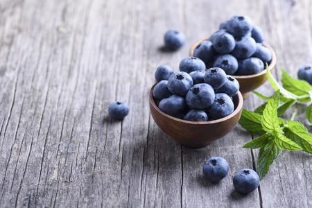 Bowl of fresh blueberries on rustic wooden table. Healthy organic seasonal fruit background. Organic food blueberries and mint leaf for healthy lifestyle.
