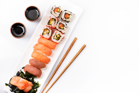 Sushi rolls set with salmon and tuna fish isolated on white background from above. Top view of traditional japanese cuisine. Asian food with chopsticks design. Stock Photo