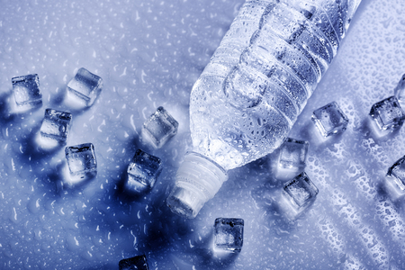 Fresh drinking mineral water in plastic bottle with ice cubes and iced drops. Healthy living concept from above.