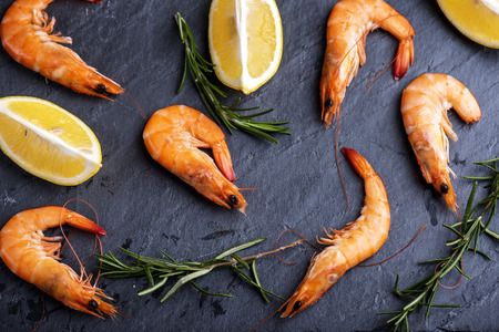 Top view of shrimps with lemon and rosemary on black background. Seafood dine cooking background.