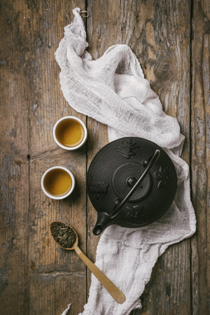 Traditional japanese herbal tea recipe prepared in cast iron teapot with organic dry herbs. Top view of asian traditional hot beverage on wooden table. Фото со стока