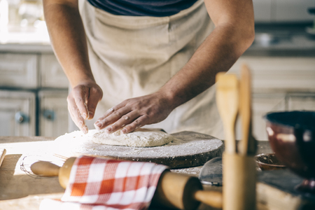 Man kneading and baking homemade pizza dough in the kitchen. Closeup on bakers hands preparing loaf of bread. Cooking and food preparation at home. Фото со стока
