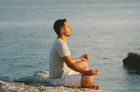Young man sitting on the sea coast, relaxing and meditating by the water at sunset. Meditation and sun gazing in nature.