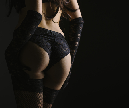 Sexy woman posing from behind in black laced lingerie.