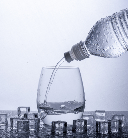 Pouring fresh drinking mineral water from plastic bottle. Glass filled with water over white background.