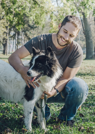 Man with his dog playing outdoor in the park. Young owner hugs his pet in nature.