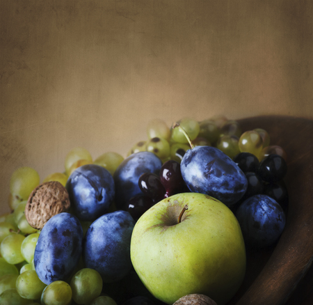 Seasonal thanksgiving fruit in wooden bowl. Vintage still life with autumn farm crops over art canvas background.