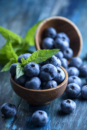 Bowl of fresh blueberries on rustic wooden table. Healthy organic seasonal fruit background. Organic food blueberries and mint leaf for healthy lifestyle.