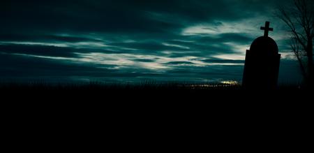 Lápida de miedo de Halloween con cielo naranja ardiente. Silueta de cementerio de terror en la noche con copyspace. 31 de octubre fondo de diseño de cartel de fiesta de halloween. Foto de archivo