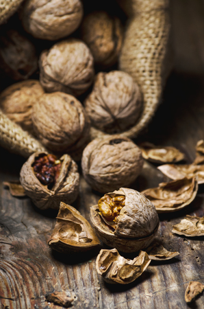 Still life with walnuts and cracked shells in vintage burlap bag. Whole walnut kernel and nutshell on rustic wooden table background.