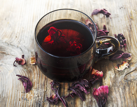 Hibiscus tea in teacup with dry hibiscus flower leaves. Organic herbal cup of tea on vintage wooden table background. Фото со стока