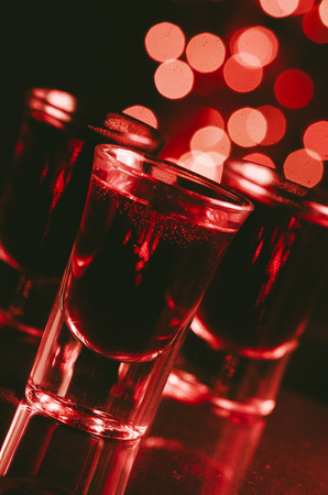Red alcohol cocktails in shot glasses over red bokeh light  background. Shots on bar counter in night club party. Imagens - 109816988