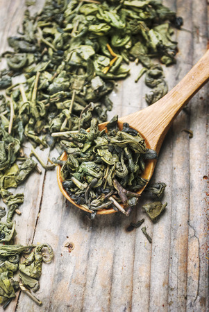 Dry green tea leaves in wooden spoon from above. Organic asian green herbal tea on vintage wooden table background.