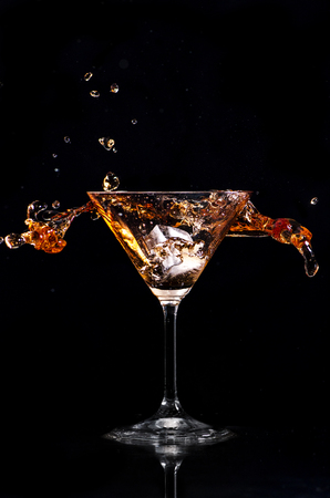 Martini cocktail splash over black background. Cocktail happy hour and night club party concept. Фото со стока