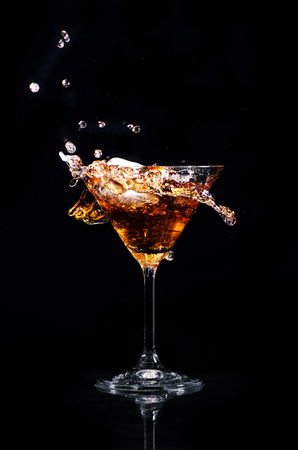 Martini cocktail splash over black background. Cocktail happy hour and night club party concept. Stock fotó