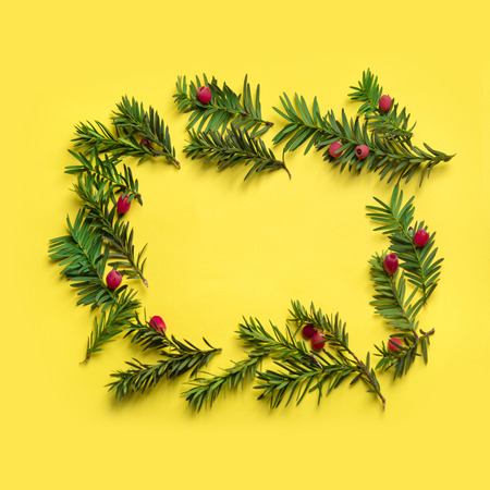 Christmas holiday frame background. Christmas tree with red decor over pastel yellow background. Top view. Merry christmas and happy new year for 2019.