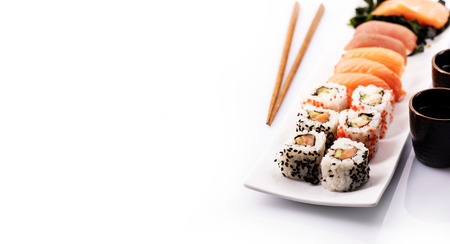 Sushi rolls set with sea weed, salmon and tuna fish isolated on white background. Traditional japanese cuisine. Asian food and drink with chopsticks design. Stock Photo