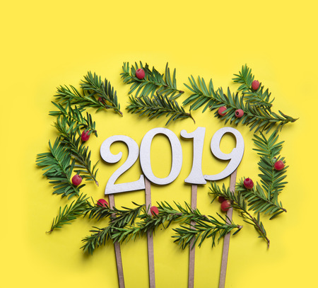 Christmas holiday background. Christmas tree with red decor over pastel yellow background. Top view. Merry christmas and happy new year for 2019.